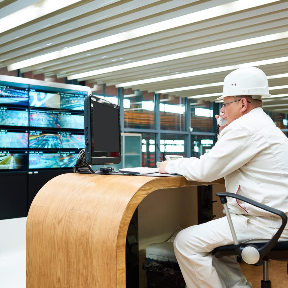 Concentrated experienced factory operator in hardhat calling shop to report important information while he working in control room